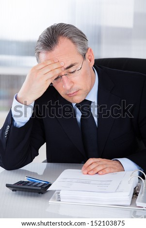 Mature Businessman Having Headache Sitting At Desk In Office - stock photo