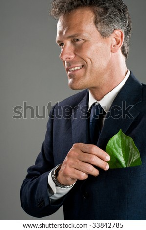 Mature businessman hold a green leaf in his suit pocket. Green business concept, take care of the environment! - stock photo