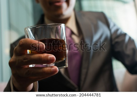 Mature businessman holding a glass of whisky in hotel. - stock photo