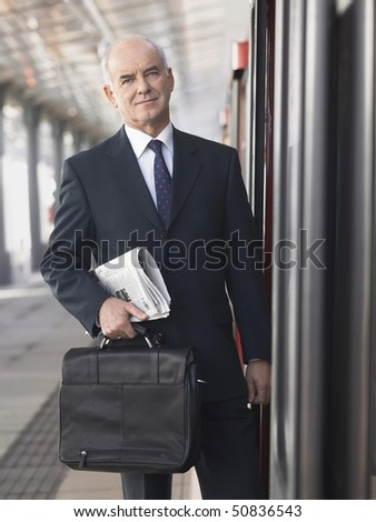 Mature Businessman holding briefcase and newspaper, standing outside train in empty Train Station - stock photo