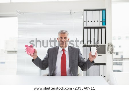 Mature businessman holding coffee and piggy bank in his office