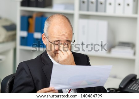 Mature businessman holding document while rubbing eyes in office - stock photo