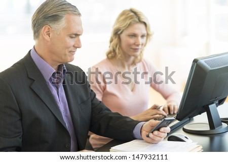 Mature businessman holding mobile phone while colleague using computer at desk in office - stock photo