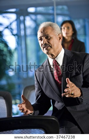 Mature businessman in boardroom meeting, colleague in background - stock photo