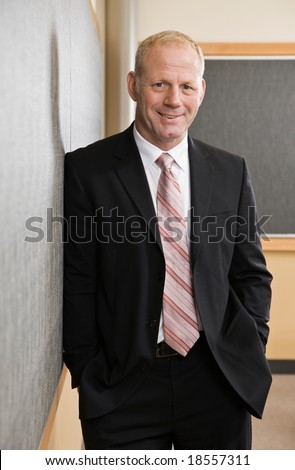 Mature businessman in full suit and tie leaning against conference room wall - stock photo