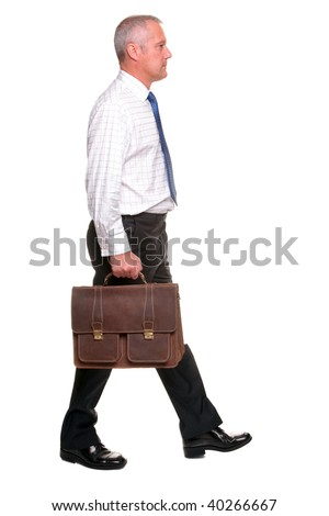 Mature businessman in shirt and tie walking towards carrying a briefcase, I've left shadow under the feet where grounded and there is a small amount of motion blur on his legs. - stock photo
