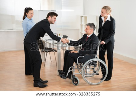 Mature Businessman In Wheelchair Shaking Hands With Colleague In The Office - stock photo