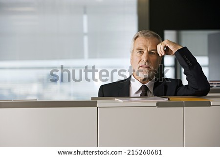Mature businessman leaning on filing cabinet in office, portrait - stock photo