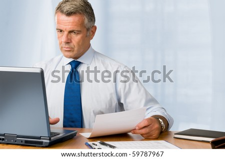 Mature businessman looking and analyzing document in his modern office at work - stock photo