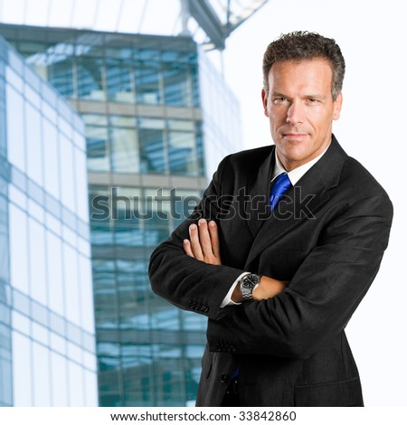 Mature businessman looking at camera with confidence against his office building - stock photo