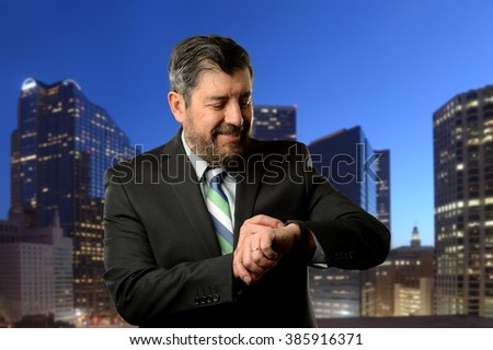 Mature businessman looking at his band wrist with buildings as background - stock photo