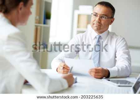 Mature businessman looking at his colleague while speaking to her in office - stock photo