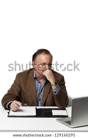Mature businessman looking at laptop with hand on chin while at work