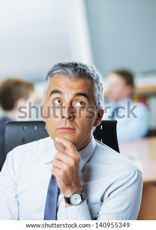 Mature businessman looking up at copy space - stock photo