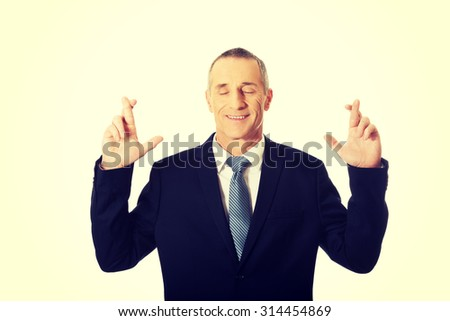 Mature businessman making a wish with fingers crossed. - stock photo