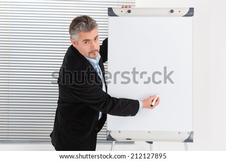 Mature businessman making presentation on flipchart. Serious businessman drawing diagram on flipchart - stock photo