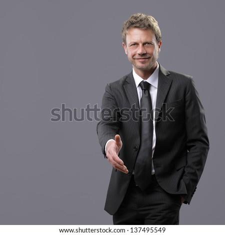 Mature businessman offering for handshake - stock photo