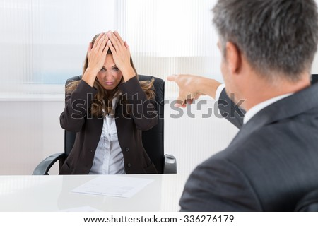 Mature Businessman Pointing To Frustrated Businesswoman In Office - stock photo