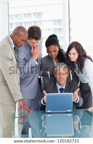 Mature businessman proudly showing the laptop screen to his team