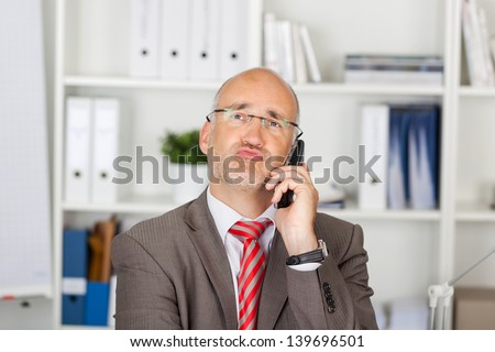 Mature businessman puckering lips while using cordless phone in office - stock photo