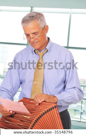 Mature Businessman Putting Papers in File Box in front of Office Window