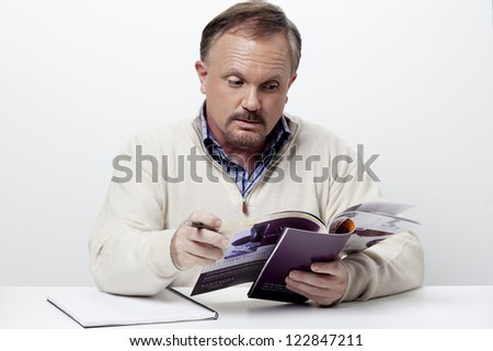 Mature businessman reading a magazine while taking a break at work