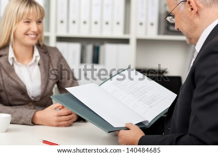 Mature businessman reading candidate's CV at office desk - stock photo