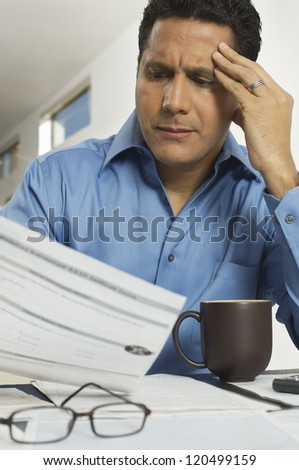 Mature businessman reading document at desk in office