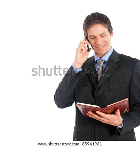Mature businessman reading his agenda while on the phone - stock photo