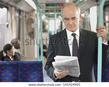 Mature businessman reading newspaper in the train with commuters sitting in background - stock photo