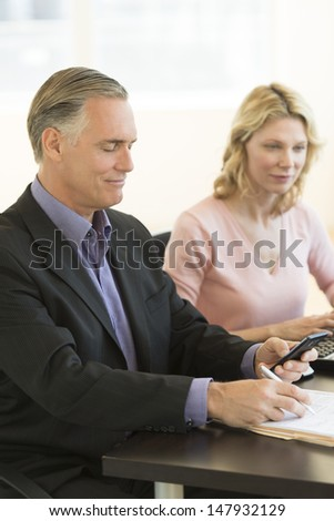 Mature businessman reading text message while female colleague working at desk in office