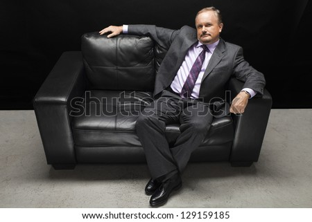 Mature businessman relaxing on couch against white background