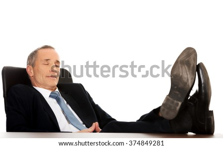 Mature businessman resting in armchair - stock photo