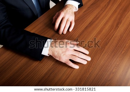 Mature businessman's hands put on the desk.