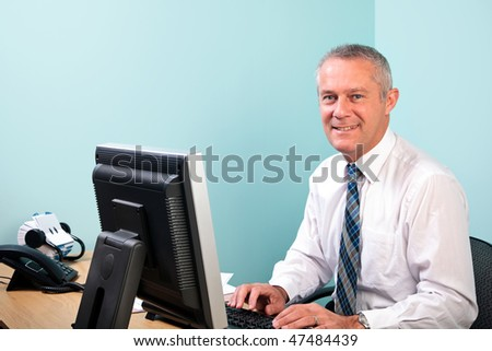 Mature businessman sat at an office desk working on his computer smiling to camera. - stock photo