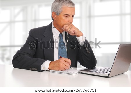 Mature businessman seated at his desk in a modern office building. In front of him is a laptop and note pad. The man is deep in thought. - stock photo