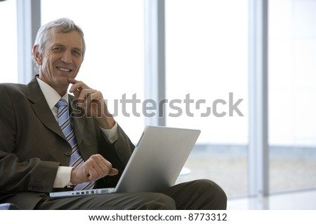 Mature businessman seated with laptop