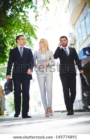 Mature businessman sharing experience with one of colleagues while going down urban street - stock photo