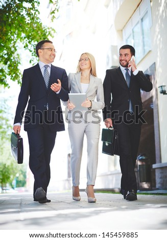 Mature businessman sharing experience with young and ambitious colleagues - stock photo