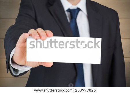 Mature businessman showing card against bleached wooden planks background