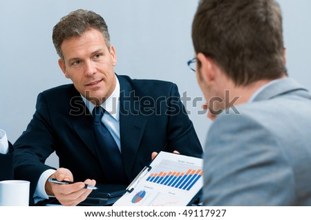 Mature businessman showing growing chart in a meeting discussion at office - stock photo