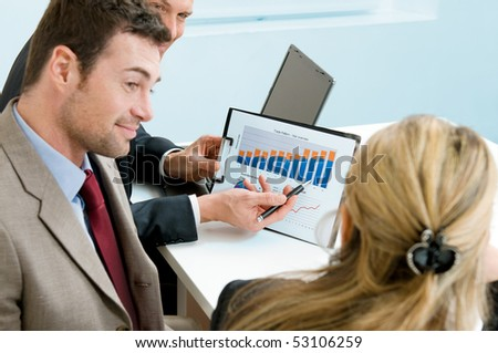 Mature businessman showing growing chart to colleagues in a meeting discussion at office - stock photo