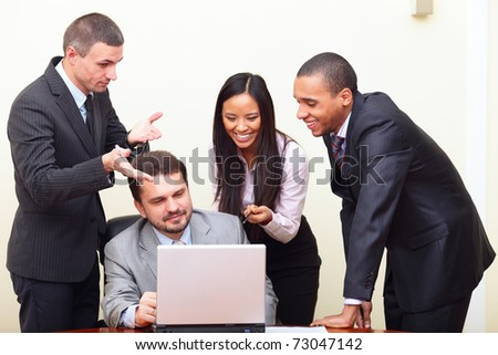 Mature businessman shows something on laptop to his multi ethnic business team