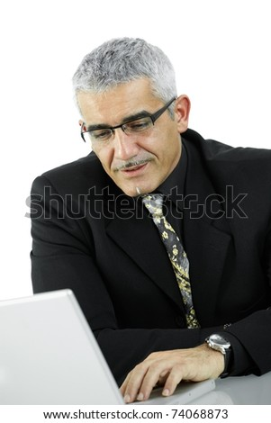 Mature businessman sitting at desk, using laptop computer, looking at screen. Isolated on white.?