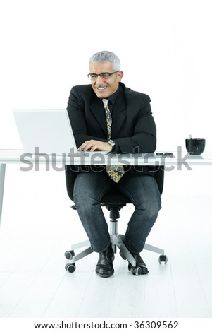Mature businessman sitting at office desk, working on laptop computer. Isolated on white. - stock photo