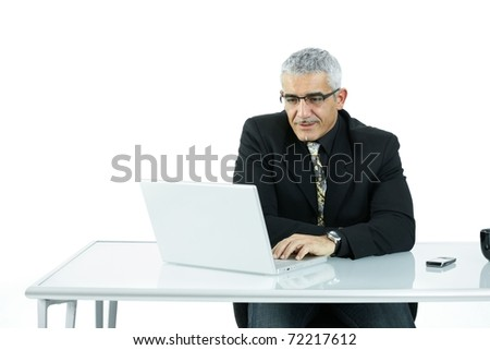 Mature businessman sitting at office desk, working on laptop computer. Isolated on white.?