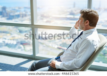 Mature businessman sitting comfortably in his office, talking on his mobile phone while looking out of his windows at the city below - stock photo