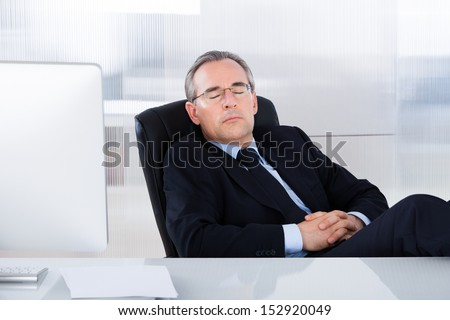 Mature Businessman Sleeping With Computer At Desk In Office - stock photo