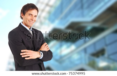 Mature businessman smiling against a blurred high tech glass building