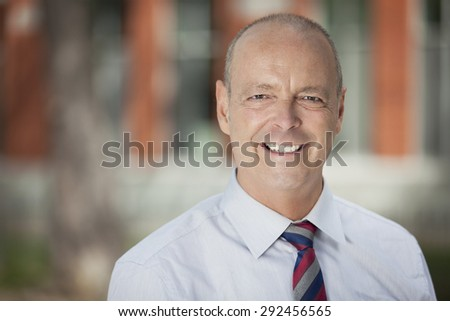 Mature Businessman Smiling At The Camera. He is outside of the office. - stock photo